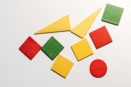 Different colorful shapes wooden on white background. Geometric shapes red, green, yellow colors, top view. Concept of geometry. Copy space. Children educational logical task. Flat lay.