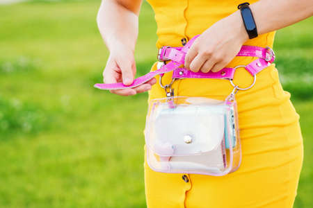 Unrecognizable Woman trendy yellow dress with transparent waist bag. Trendy elegant casual outfit. Details of everyday look. Street fashion. Close-up. Copy space for text