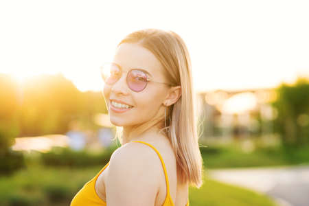 Sunburnt portrait of a beautiful young woman in stylish glasses. Hot summer day. Fashionable girl