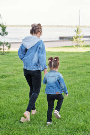 Lifestyle portrait of mom and daughter happy on the outside. Family time together. Modern family look denim. Mothers Day, love family, parenthood, childhood concept. Back view