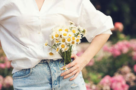 Young unrecognizable woman dressed in blue jeans and white shirt holding small bouquet of flowers, close up. Camomile background copy space