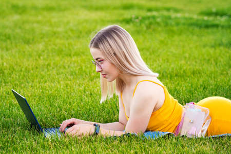 Girl freelancer. Attractive woman using laptop lying on lawn in park surfing the net or preparing for exams. Technology, education and remote work concept. Freelance Worker.