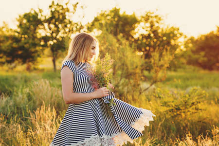 Portrait eco-friendly woman in striped sundress on meadow with bouquet of wildflowers in hand dancing on green field in sunset and sun glare. Summer evenings in nature. Background. Soft focus