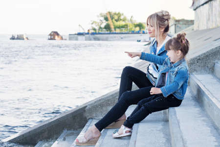 Mother and child walking on sea promenade street. Travel and holiday. Family time together. Modern Denim look. Lifestyle portrait of mom and daughter