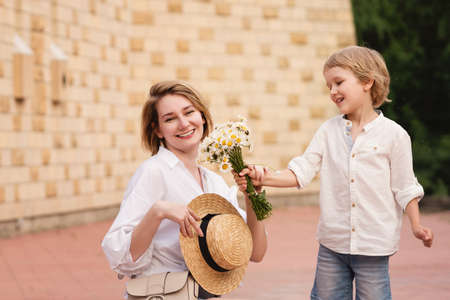 Little cute boy gives his mom a bouquet of daisies. Young gentleman. Lifestyle portrait of mom and son. Family time together