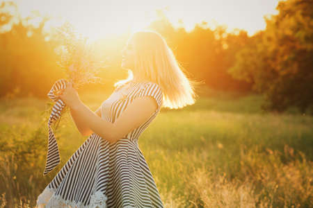 Portrait eco-friendly woman in striped sundress on meadow with bouquet of wildflowers in hand dancing on green field in sunset and sun glare. Summer evenings in nature. Background. Space for text Banco de Imagens