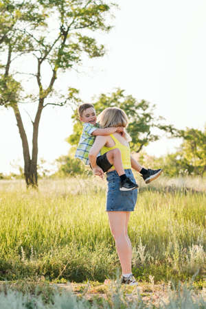 Young cheerful family in the meadow. Mom and son schoolboy spend time together and have fun in nature. Leisure. Summer holidays. Summertime. Happy childhood and motherhood