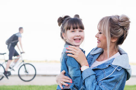 Happy mother and cute daughter play and talk in the park on summer day. Mothers Day, love family, parenthood, childhood concept. Family time together. Denim look Banco de Imagens