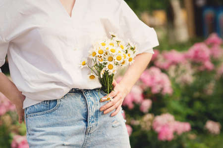 Cute little daisies bouquet of simple flowers in unrecognizable womans hands on white background with copy space. Banco de Imagens
