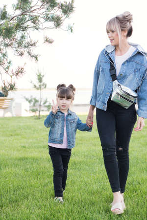 Lifestyle portrait of mom and daughter happy on the outside. Family time together. Modern family look denim. Mothers Day, love family, parenthood, childhood concept