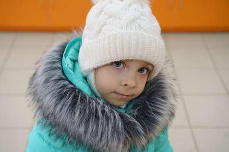 Close up portrait of a cute little girl in winter outerwear. Banco de Imagens