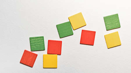 Different colorful squares wooden on white background. Geometric shapes red, green, yellow colors, top view. Concept of geometry. Copy space. Children educational logical task. Flat lay. Banco de Imagens