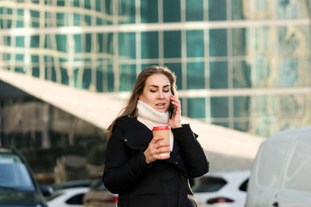 Portrait busy modern pretty woman stands on sunny day talking on smartphone. Attractive business lady holding takeaway coffee, using mobile phone. Business woman on background modern business center