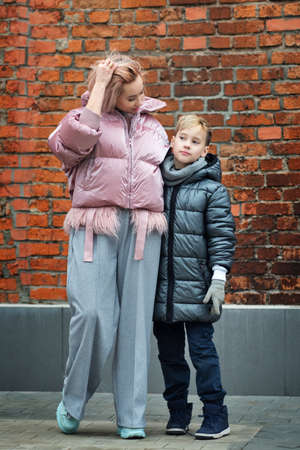 Loving young mother embracing schoolboy hipster son enjoying time together at city street, happy family single mom. To get together