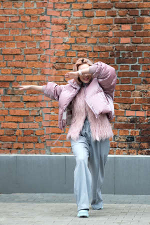Trendy hipster young woman making dab gesture, having fun on the city street. Brick background. Lifestyle portrait
