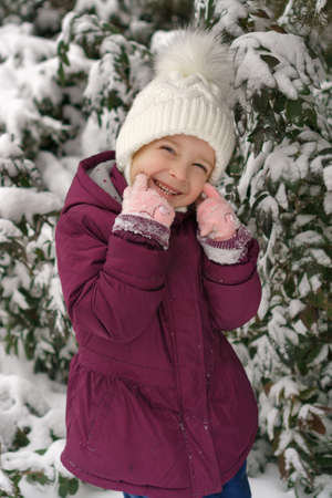 Portrait of a little cute emotional girl on a background of a snowy Christmas tree. Walk on a winter snowy day. Happy childhood. Games, freedom and carefree