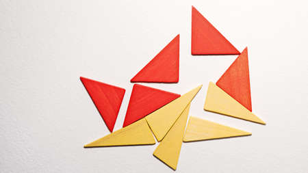Different colorful triangles wooden on white background. Geometric shapes red, yellow colors, top view. Concept of geometry. Copy space. Children educational logical task. Flat lay.