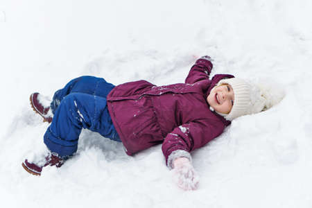Full length portrait of a little playful girl in the snow. She has fun and leads a healthy lifestyle. Walk on a winter snowy day. Happy childhood. Games, freedom and carefree