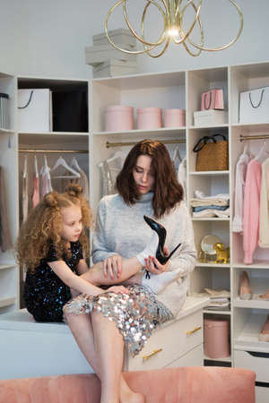 Stylish mom and daughter gathered for party. Daughter trying on mother shoes sitting on closet in dressing room. Personal wardrobe room. Nothing to wear. Choosing shoes for special occasion. . Zdjęcie Seryjne