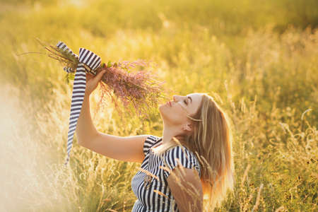 Beautiful blonde woman in striped sundress on meadow with bouquet of wildflowers sitting on a sunset. Summer evenings in nature. Background. Space for text