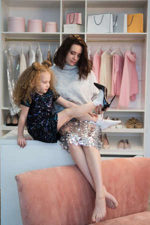 Stylish mom and daughter gathered for party. Daughter trying on mother shoes sitting on closet in dressing room. Personal wardrobe room. Nothing to wear. Choosing shoes for special occasion.