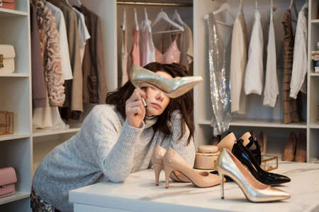 Depressed woman standing near wardrobe full of clothes, having difficult choice not knowing what to put on shoes. Nothing to wear concept. Choosing shoes for special occasion.
