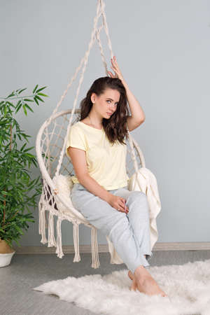 Young Woman Wearing Pyjamas Chilling At Home In Comfortable Hanging Chair. Spend Free Lazy Time At Home Concept