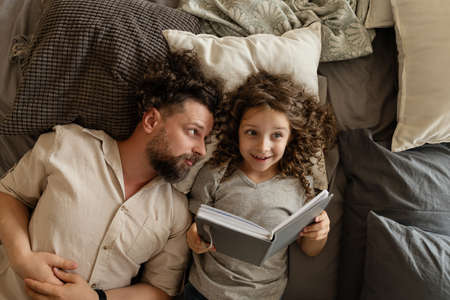 Happy family. Father puts his daughter to bed. Reading before bed. Time for a magical story. Spend time together. Dad and daughter at home Stock fotó