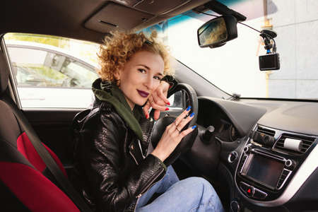 Portrait curly hair woman siting in her own automobile, keeping hands on wheel, wearing a rock black style. People, driving, transport concept. Sideways shot. Urban fashion concept