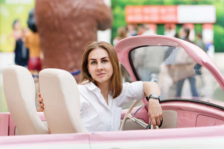 Adorable girl In Vintage Convertible. Portrait Of Woman Enjoying Road Trip In Open Top Classic Car. Banco de Imagens