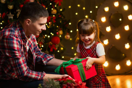 Cute little girl is happy New Year gifts. Father with daughter in magic night. Happy family opening presents and having fun on Christmas Eve