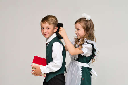 Portrait two elementary school students in uniform with books and tablet pc. New technologies for teaching. Online Education Gadgets. Success, creative ideas and innovation technology Banco de Imagens