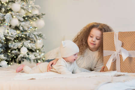 Chidren christmas morning. Merry Christmas and Happy Holidays. Cheerful cute childrens having fun near tree. Loving family with presents in room. Christmas eve at home Banco de Imagens