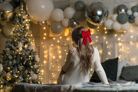 Unrecognizable girl with a bowknot of red ribbon on a xmas background - hairstyle concept. View from the back. Merry Christmas and Happy Holidays. Christmas eve at home