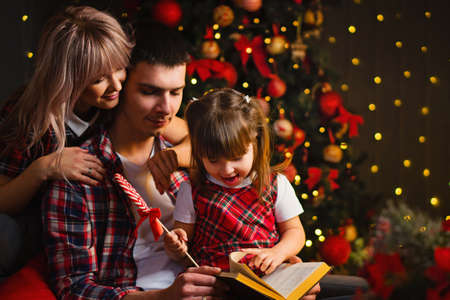 Mom, Dad and Daughter reading Magic Book At Home Near Chritmas Tree. Magic Lights In Night Xmas Tree Interior. Lollipop. Celebration Atmosphere.