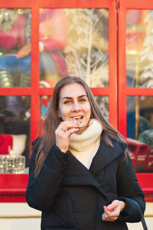 Cheerful young woman posing with gingerbread at Christmas market. Merry Christmas and Happy Holidays. Christmas Eve Banco de Imagens