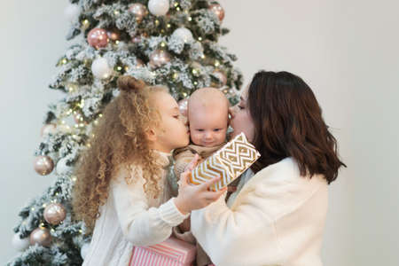 Family In Cozy Home Clothes In Lounge At Home Opening Gifts On Christmas Day. Single mom, Daughter and Toddler Banco de Imagens