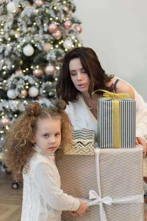 Family christmas morning. Mom and daughter open gifts. Girls greet Christmas among boxes of gifts and Christmas lights.