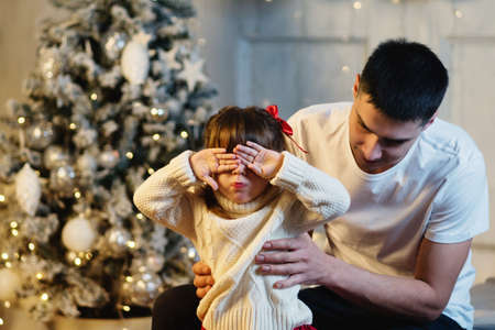 Cozy Xmas Morning Family At Home Near Chritmas Tree. Celebration Atmosphere. Magic Lights Christmas Tree Interior.