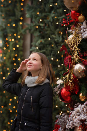 Teen girl walking winter city decorated with lights. Merry Christmas and Happy Holidays. Christmas eve