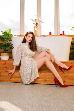 Young Glamour Girl In Elegant Dress Combination And Red Stiletto Heels Sits Near White Modern Bath At Window Bathroom