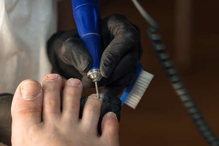 Hardware pedicure, preparation of the nail plate for applying gel polish. Master chiropody shapes the nails . Female patient in the process of hardware pedicure procedure. Foot care
