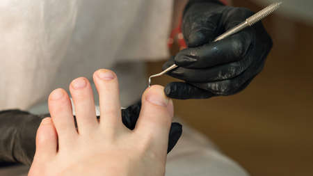 Process of professional pedicures. The concept of beauty and health. Chiropody master provides high quality services in beauty salon. Banco de Imagens