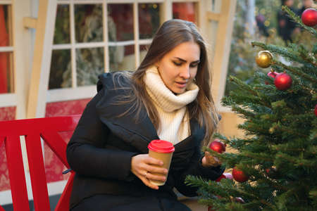 Girl drinks takeaway coffee and walks at the Christmas market on a sunny evening. Feeling happy in big city. Festive mood.