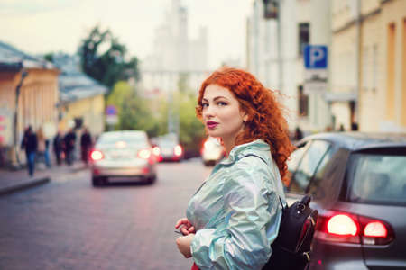 Romantic Curly Red-haired Girl Walking Through Town At Evening