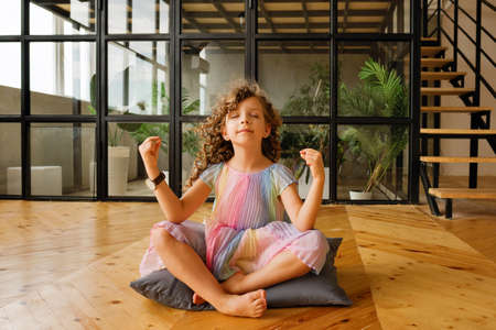 Child Girl Playing Meditates in Yoga Pose. Yoga Exercise At Home. Breathing Exercise. Relaxing Healthcare Concept.