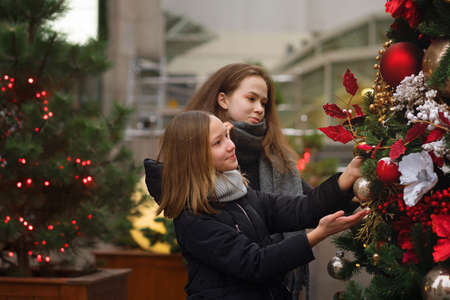 Two female best friends on Christmas Market. Adorable sisters having fun together on traditional Christmas fair. Winter time with family. Girls enjoying the scenery and atmosphere on Xmas market. Banco de Imagens