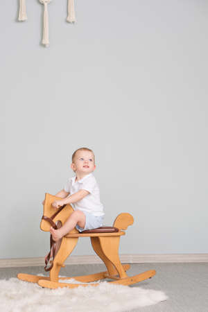 Child Sitting On Ride On Toy In Playroom. Toddler Baby Boy Riding Swinging On Rocking Chair Toy Horse