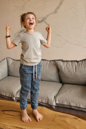 Funny girl Showing Rock Sign. Smiling Preteen in Jeans and Tee Happily Having Fun and Posing on the Table.