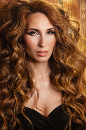 Portrait glam luxury redhead woman with curly hairstyle. Beautiful girl and long wavy hair. Beautiful female model in black dress.